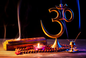 Om symbol incense smoke candle and japa mala on wooden table at black background